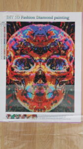 multi-coloured skull diamond painting being completed as a hobby