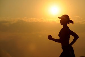 woman running for health at sunset