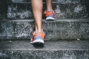photo of a runners feet and ankles from behind as they run up steps