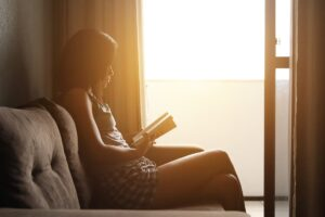 Woman sat reading a book in front of a window
